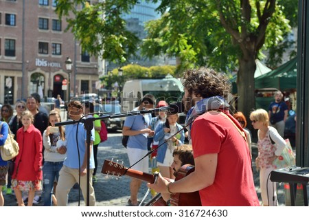 BRUSSELS, BELGIUM, JULY 10, 2015: Street musician gives concert on the street in historical center of Brussels