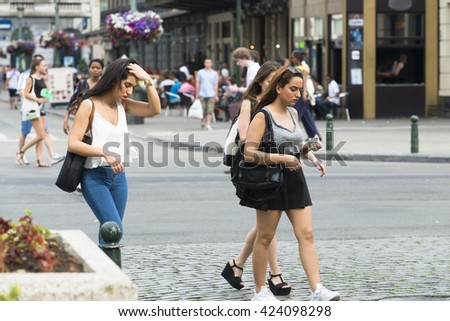 BRUSSELS, BELGIUM - JULY 4, 2015: Three young women, one with an iPhone in hand, walk down one of the streets of the city. - stock photo