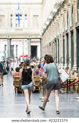 BRUSSELS, BELGIUM - JULY 4, 2015: Two women walk the Galeries Royales Saint Hubert, in the city center, the first commercial galleries of Europe. - stock photo