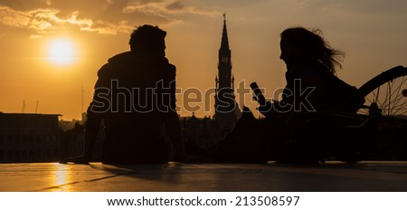 BRUSSELS, BELGIUM - JUNE 14, 2014: Silhouette of pair ower the town on Monts des Arts in evening.