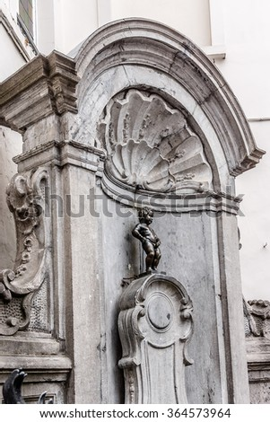 BRUSSELS, BELGIUM - JUNE 19, 2014: The Mannekin Pis (le Petit Julien, designed by Hieronymus Duquesnoy the Elder, 1618 or 1619), is a famous statue a naked little boy urinating into a fountain's basin - stock photo