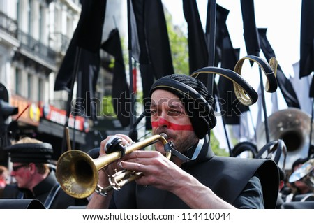 BRUSSELS, BELGIUM-MAY 19: Unidentified participant in fancy dress plays music for visitors of Zinneke Parade on May 19, 2012 in Brussels. This parade is a biennial urban artistic free-attendance event - stock photo
