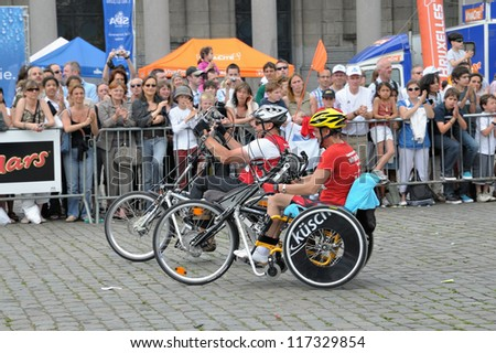 "BRUSSELS, BELGIUM-MAY 31: Unidentified participants in special wheelchairs arrive to finish of 30th ""20 km de Bruxelles"" Marathon on May 31, 2009 in Brussels, Belgium. - stock photo"