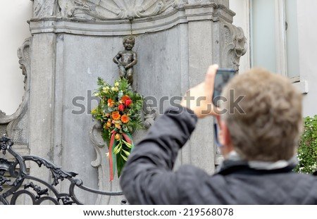 BRUSSELS, BELGIUM-SEPTEMBER 21, 2013: Manneken Pis with flowers prepared for a ceremony of award of costume and a tourist taking his picture - stock photo