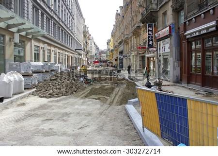 BRUSSELS, BELGIUM - SEPTEMBER 14, 2011: Street and sidewalk reconstruction in the process, pedestrians continue using sidewalk during reconstruction. - stock photo