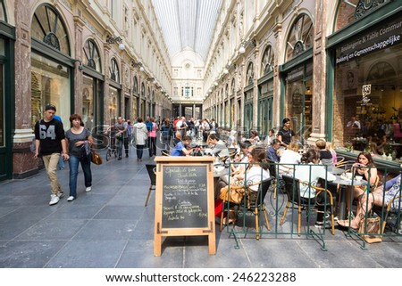 BRUSSELS - JULY 30: People in the Royal Galleries of Saint-Hubert on July 30, 2014 in Brussels. Opened in 1847, it is one of the oldest shopping galleries in Europe. - stock photo