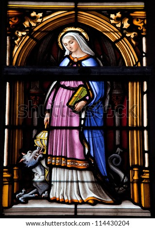 BRUSSELS - JULY 26: Stained glass window depicting Saint Gudula in the cathedral of Brussels on July, 26, 2012. - stock photo