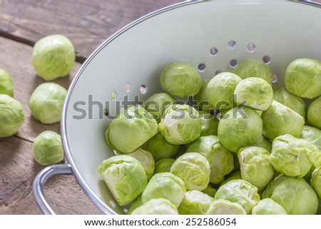 Brussels sprouts in a sieve on a wooden table - stock photo
