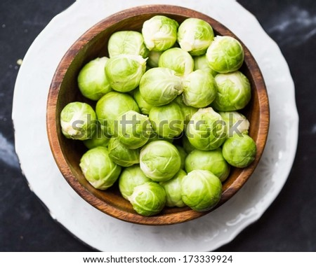 Brussels sprouts in a wooden bowl on the table, tasty, healthy vegetable bio products - stock photo