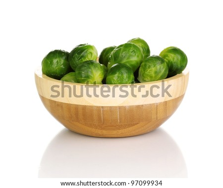 Brussels sprouts in wooden bowl isolated on white - stock photo