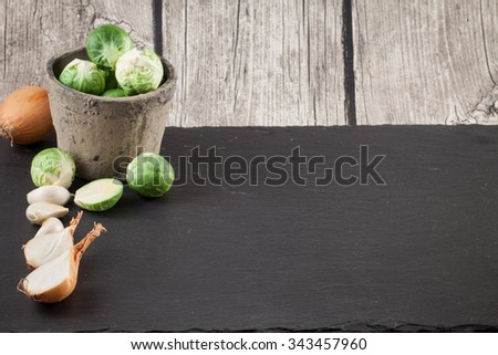 brussels sprouts, tomatoes and onions on a black background - stock photo