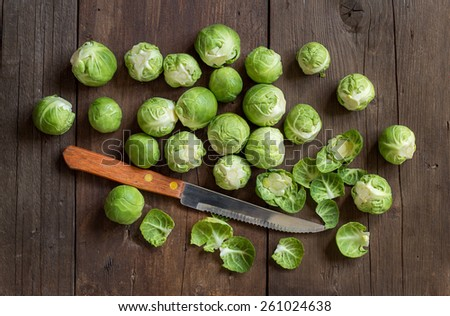 Brussels sprouts with leaves and knife on wood - stock photo