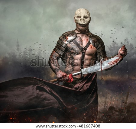 Brutal artistic male in the skull mask holds sword in the dust batterfield background.