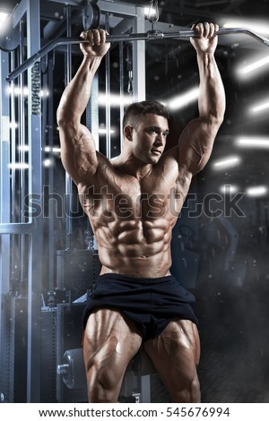 Brutal athletic attractive muscular bodybuilder guy with six pack prepare to do exercises with athletic trainer in a gym