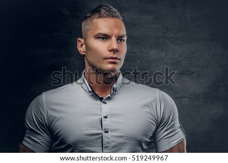 Brutal athletic male vogue model dressed in a white shirt on grey background.