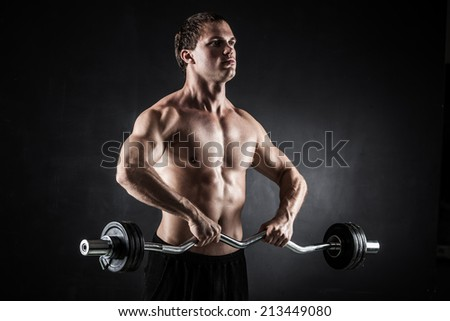 Brutal athletic man pumping up muscles with barbell - stock photo