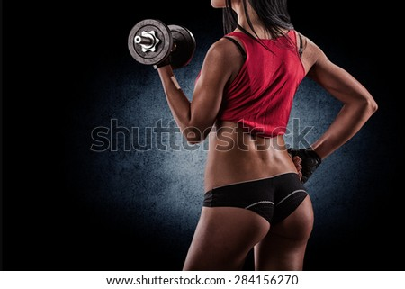 Brutal athletic pumping up muscules with dumbbells - stock photo