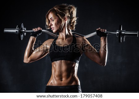 Brutal athletic woman pumping up muscles with barbell - stock photo