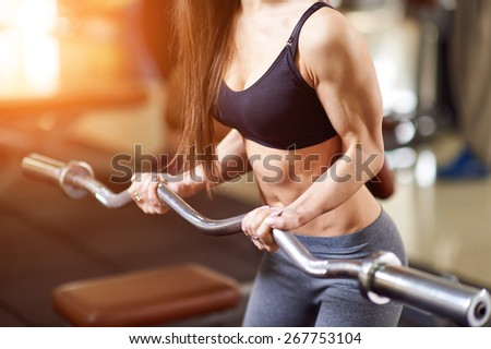 Brutal athletic woman pumping up muscles with barbell. Attractive fitness woman, trained female body. Brunette sexy fitness girl in black and gray sport wear with perfect body in the gym. - stock photo