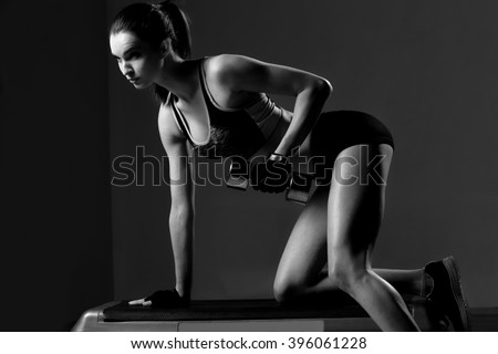 Brutal athletic woman pumping up muscles with dumbbells. - stock photo