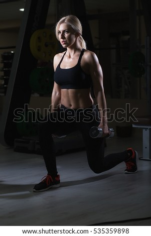 Brutal athletic woman pumping up muscles with dumbbells.