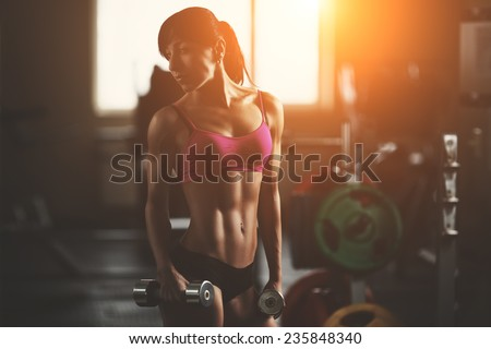 Brutal athletic woman pumping up muscles with dumbbells. Brunette sexy fitness girl in pink sport wear with perfect body in the gym posing before training set. Attractive fitness woman - stock photo