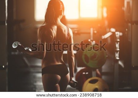 Brutal athletic woman pumping up muscles with dumbbells. Brunette sexy fitness girl in pink sport wear with perfect body in the gym posing before training set - stock photo