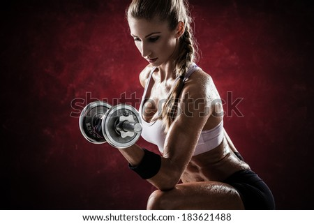 Brutal athletic woman pumping up muscles with dumbbells on red background - stock photo