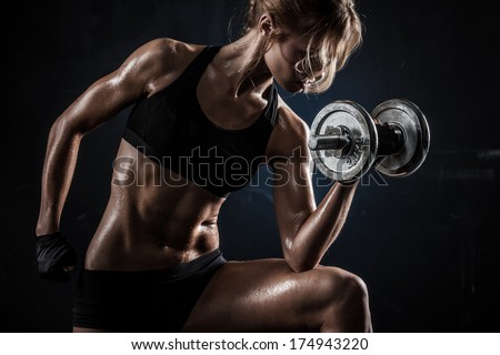 Brutal athletic woman pumping up muscules with dumbbells - stock photo