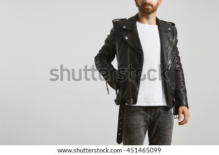 Brutal attractive bearded biker in black tailored motorcycle leather jacket poses in white blank t-shirt from premium thin cotton, isolated on white mockup