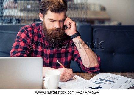 Brutal bearded man talking on cell phone