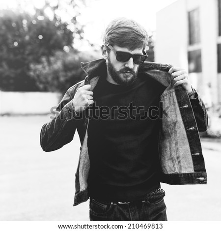 Brutal black and white portrait of a fashionable man with a beard and glasses