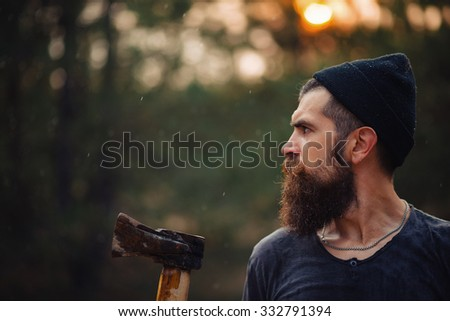 Brutal brunette bearded man in warm hat with a hatchet in the woods on a background of trees, half-face