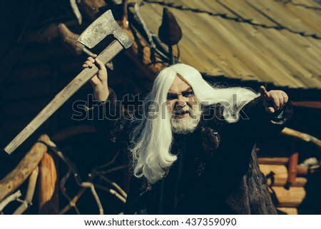 Brutal druid old man with long silver hair and beard in fur coat with axe in hand on log house background
