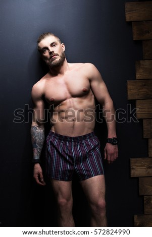 Brutal guy with a beard, athletic build. In shorts. Fashion shoots in the Studio.