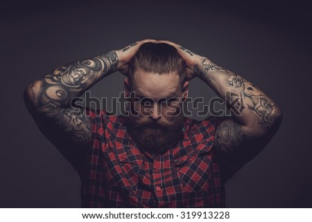 Brutal guy with beard and tattooes holding his head. Isolated on grey background. - stock photo
