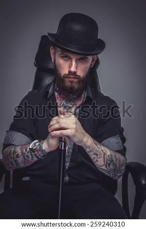 Brutal handsome man with tattooed body holding cane