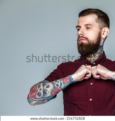 Brutal handsome man with tattooed body. Isolated on grey - stock photo