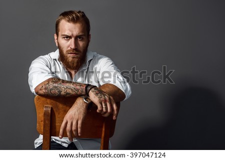Brutal handsome man with tattooed body sitting on chair - stock photo