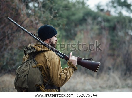 brutal hunter, bearded man in warm hat with a gun in his hand, a knife and a backpack in the wild forest in the autumn