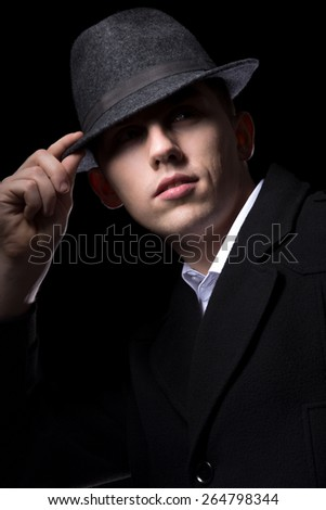 Brutal looking man hiding his eyes in the darkness, touching his hat, greeting, unrecognizable person, low key studio shot