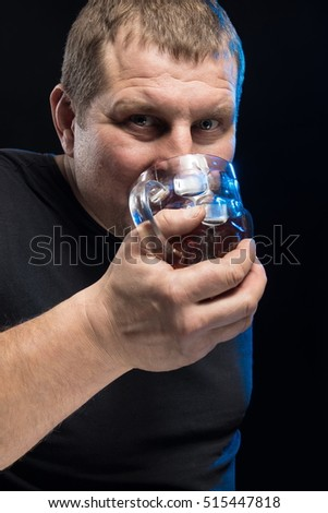 Brutal male actor with a glass of beer on a black background. Caricature change.