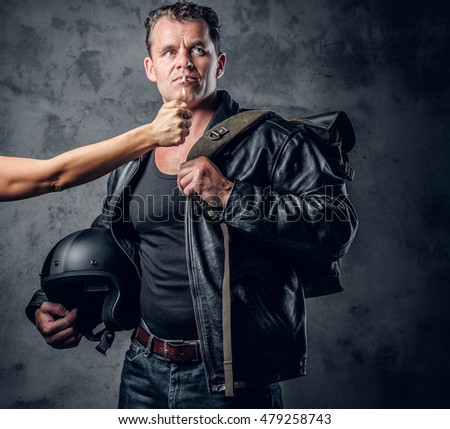 Brutal male in leather jacket holds motorcycle helmet and lights up a cigarette from woman arm.