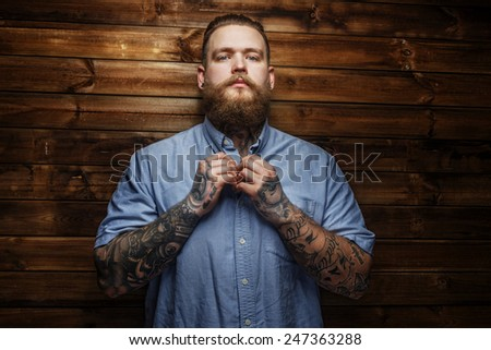 Brutal male with beard and tatooes buttons up his t-shirt - stock photo