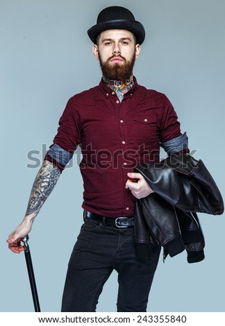 Brutal male with many tattoes on his body standing holding cane - stock photo