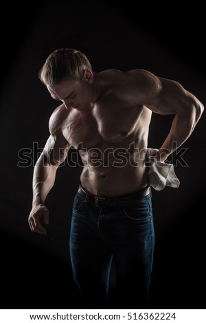 Brutal man bodybuilder athlete towel in hand on a black background.