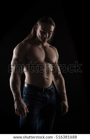 Brutal man bodybuilder athlete with long hair on a black background.