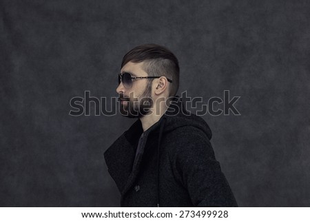 Brutal man with a beard and fashionable hairstyle, sunglasses