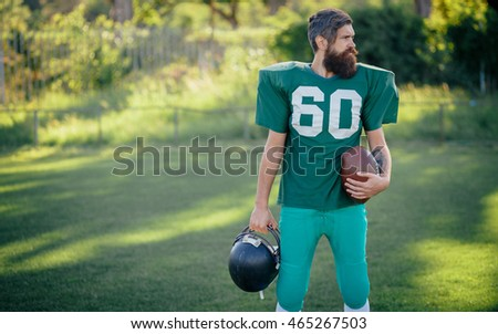 Brutal man with a long beard and mustache in the shape of an American football player with helmet and Ball on the training ground
