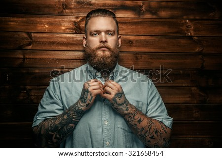 Brutal man with beard and tatoos possing over wooden wall. - stock photo